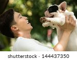 Stock photo smiling owner holding his friendly pet with affection 144437350