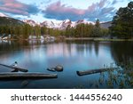 A duck sits on a log at sunrise on Sprague Lake located in Rocky Mountain National Park in Colorado