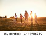 Vacations in countryside. Silhouettes of family with dog walking on meadow at sunset