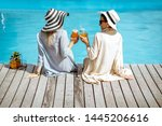 Two women in hats and shirts sitting with drinks on the poolside, back view