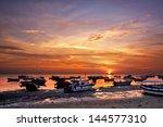 sunrise over fishing boats in... | Shutterstock . vector #144577310