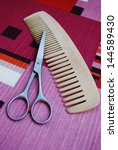 Professional scissors and wooden comb on colorful background - stock photo