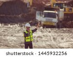Small photo of Portrait of asian male supervisor in mine soil field location operation a radio or walkie talkie to communication with co worker team with exavator and dumb truck digging limestone as background