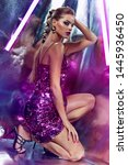 Small photo of Beautiful young tanned girl in a pink shiny dress in the studio on a silver background with a pink and purple hue.Beauty, fashion, silver, sparkles, hairstyle, makeup, glamor, luxury, neon, glow.