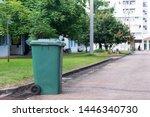 Green Garbage Bin In Front Of...