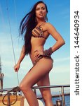 Portrait of a gorgeous long-haired brunette in stylish swimsuit with awesome tan standing on the aft of a sailing yacht. Sunny summer day. Bikini fashion. Outdoor shot - stock photo