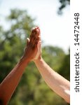 """african american and European american men do a """"high five"""" hand clap outside - stock photo"""