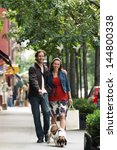 Stock photo full length of a happy couple walking dog on sidewalk 144800338