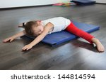 a child in a gym with a yoga...