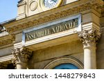 "Small photo of Close-up view of the sign ""Assemblee Nationale"" in golden letters on the pediment of the southern entrance of the Palais Bourbon, seat of the French National Assembly in Paris, France, on a sunny day."