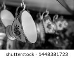 Small photo of Black and white close up of a fine china teacup hanging in a row of teacups in a cabinet, blurred background. Chic interior. Retro, vintage.