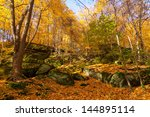 Rock ledges under a canopy of golden leaves - stock photo