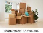 Stack of moving boxes in new house - stock photo