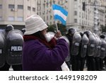 Small photo of Buenos Aires, Argentina, 2019-07-09: On the day of independence, a woman with an Argentine flag in front of a strong repressive operation on the obelisk