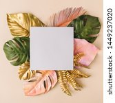 Small photo of Creative layout made of colorful and golden tropical leaves and palms on beige background. Minimal summer exotic concept with copy space. Border arrangement background.