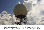 Doppler weather radar against blue sky with white clouds and sun reflecting off of sphere. Located at a National Weather Service site. Includes copy space.