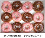 Small photo of Top view flat lay of one dozen glazed donuts, alternating strawberry and chocolate in a white box isolated. Are donuts becoming a new fad or the new trend. Gourmet style fancy donuts.