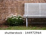 Very old bench with white flowers near the wall in nostalgic atmosphere - stock photo