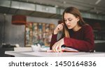 Stock photo concentrated female student sitting at cafeteria reading interesting book for literature homework 1450164836