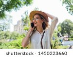 Small photo of Portrait of a young single-minded blonde woman talking on the phone and walking around the city outdoors