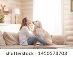 Stock photo young pretty woman in casual clothes hugging her beloved big white dog sitting on the sofa in the 1450573703