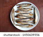 Stock photo smoked fish baltic herring in geometrical composition on round plate flat lay close up food photo 1450639556
