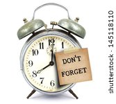 Small photo of text don't forget on vintage retro alarm clock and short note on white background