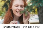 Red-haired girl eating pine needles. Parody of vegetarian. Funny redhead veggie is very hungry. Beautiful ginger woman on diet wants to eat much. Smiling girl wants to taste greens.