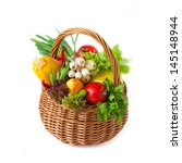 Fresh kitchen garden vegetables in a wicker basket on a white. - stock photo