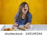 Small photo of Cute little girl with long hair has blue sweater and an expression of repudiation of a pizza