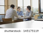 Stock photo male and female doctors communicating with nurse on work break in cafeteria 145175119