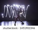 Modern Dance performer dancing with a neon blue light while making gracious moves and spectacular body art expressions, long exposure motion blur
