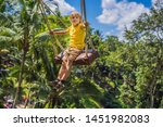 young boy swinging in the... | Shutterstock . vector #1451982083