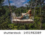 young woman swinging in the... | Shutterstock . vector #1451982089