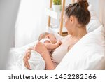 Small photo of Young woman breastfeeding her baby at home