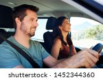 Mid adult white man driving car, his wife beside him in front passenger seat, close up, side view - stock photo