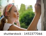 girl paints a cardboard house... | Shutterstock . vector #1452377066