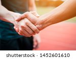 Small photo of Concept of Negotiating business or competition and handshake Gesturing People Connection Deal. close up hand of young man shaking hands with rival or partner or customer on modern outdoor,fair play