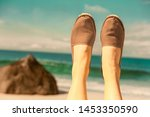 Stock photo legs with espadrilles in beige in front of water 1453350590