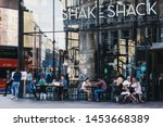 Small photo of London, UK - July 15, 2019: People sitting at the outdoor tables of Shake Shack in Victoria station. Shake Shack is an American fast food restaurant chain that opened first shop in UK in 2013.