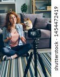 Stock photo happy girl creative vlogger recording video with adorable dog at home sitting on floor talking 1454472419