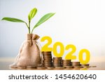 Small photo of Wood block 2020 and Coins in sack with small plant tree. Pension fund, 401K, Passive income. Investment and retirement. Business investment growth concept. Risk management. Budget 2020.