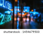 Small photo of Display of Stock market quotes with city lights reflect on glass