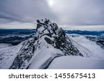 View of a winter alpine like mountain landscape of High Tatras, Slovakia. High rocky ridge and summit or peak of Koncista and other peaks in Vysoke Tatry National Park. Snow covered high alpine peaks.