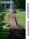 Trench Dug in the Green Yard by a Trench Digger for PVC Water Drainage Pipe