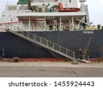 Small photo of a crew is walking on a gangway ladder after they checked draft. they work on a cargo ship which is quite big. gangway net was put properly, all secure with the ship's rail to prevent man fall in water