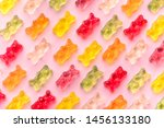 Small photo of Flat lay composition with delicious jelly bears, jelly bears pattern on pink background