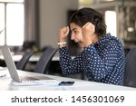 Small photo of Excited millennial employee sit at desk witness online lottery win on laptop, scream from happiness, happy indian woman winner look at computer screen hit jackpot, female office worker read good news