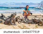 Ecotourism tourist photographer taking wildlife photos on Galapagos Islands of famous marine iguanas. Focus on marine iguana. Woman taking pictures on Isabela island in Puerto Villamil Beach.