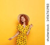 Pretty carefree lady dances and looks with eyes full of happiness, tender smile, has slim figure, wears straw headgear, stylish polka dot dress, has perfect mood, models agaisnt yellow background